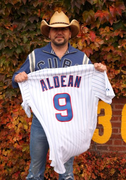 Country singer Jason Aldean poses with a Chicago Cubs baseball shirt during a news conference at Wrigley Field to announce his 2013 Night Train Tour on Thursday, Oct. 18, 2012, in Chicago. (Photo by Barry Brecheisen/Invision/AP)