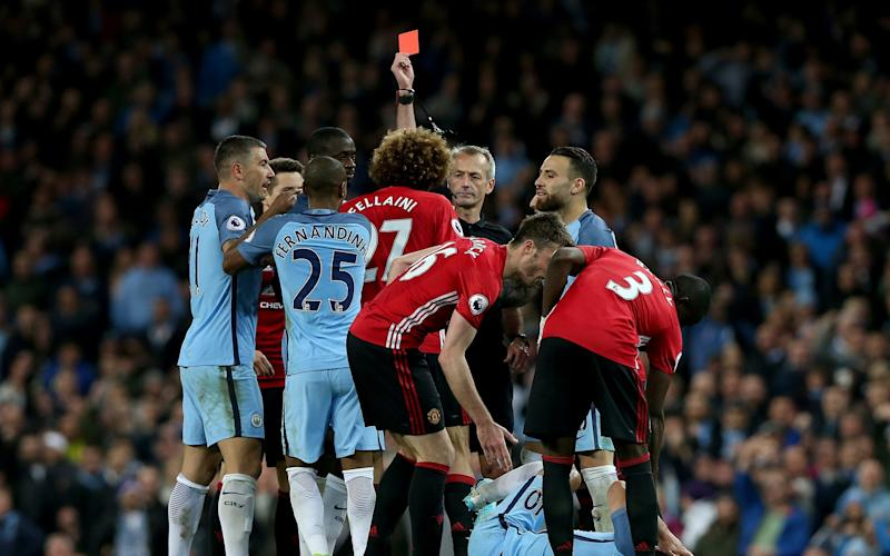 Manchester United's Marouane Fellaini (C) is sent off for a head butt on Manchester City's Sergio Aguero - Credit: EPA
