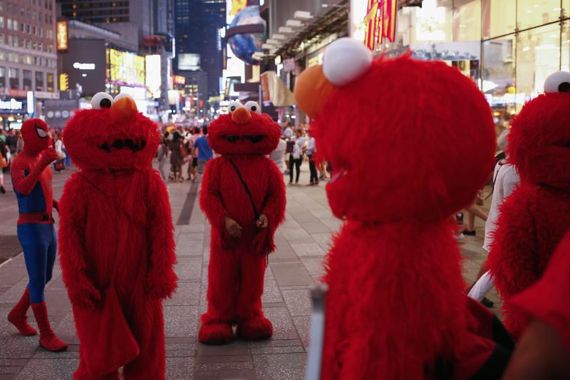Jorge, an immigrant from Mexico, stands amidst other people, all dressed as the Sesame Street character Elmo, while they look to make tips for photographs in Times Square in New York