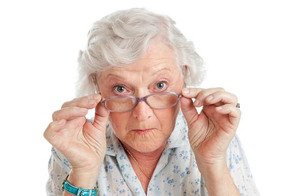 white-haired senior woman peering over her glasses with interest