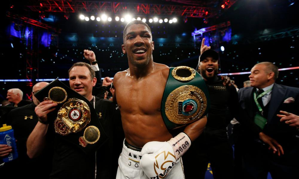 Anthony Joshua celebrates with trainer Robert McCracken after winning the fight.