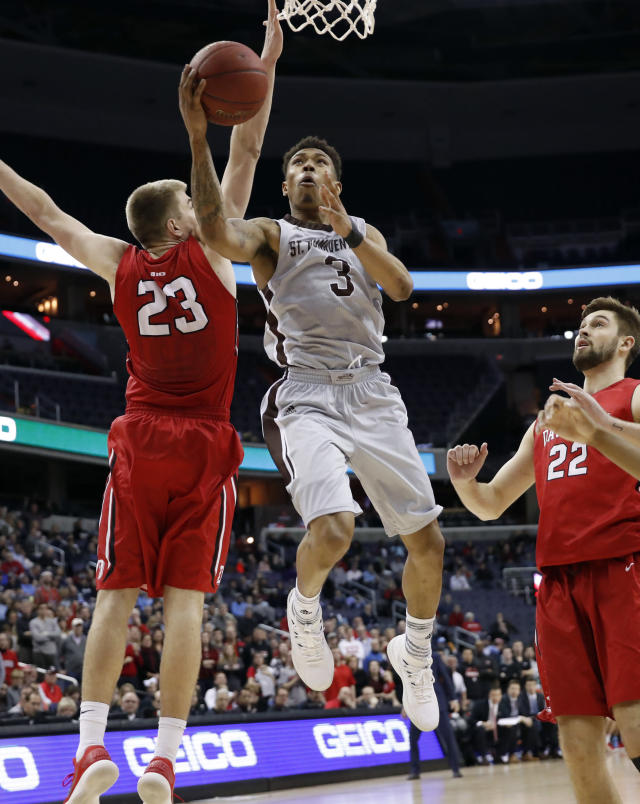 St. Bonaventure guard Jaylen Adams (3) shoots between Davidson forwards Peyton Aldridge (23) and Will Magarity (22) during the second half of an NCAA college basketball game in the semifinals of the Atlantic 10 Conference tournament, Saturday, March 10, 2018, in Washington. Davidson won 82-70. (AP Photo/Alex Brandon)