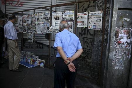 A man reads newspaper headlines in Athens