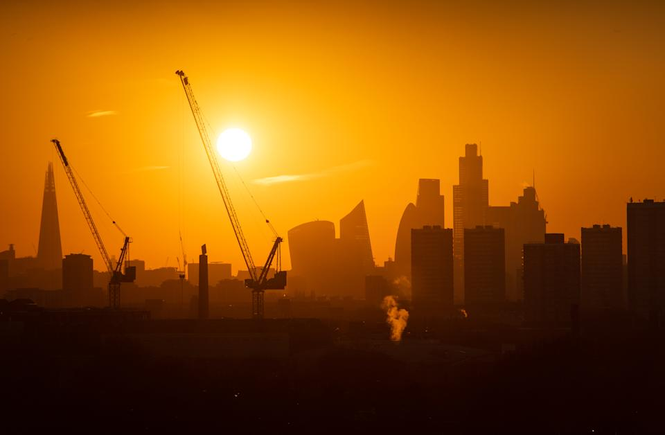 The sun sets behind tower cranes and the London skyline, including the Shard (left) and skyscrapers in the city financial district of London. PA Photo. Picture date: Tuesday January 21, 2020. Photo credit should read: Dominic Lipinski/PA Wire