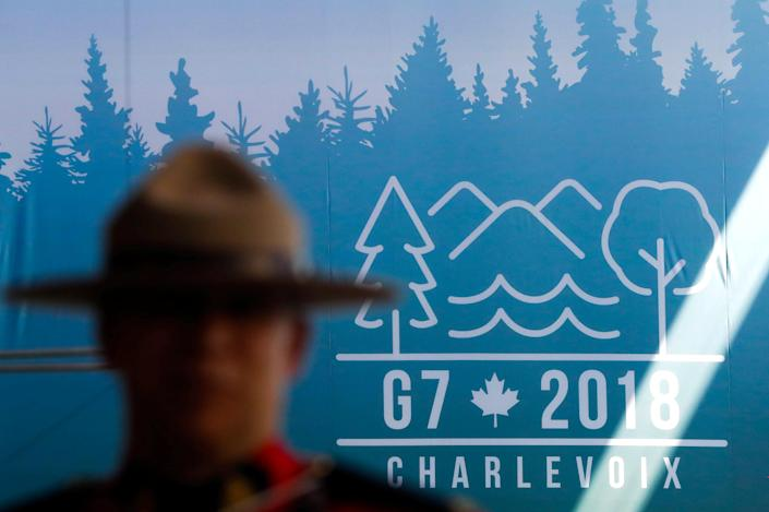 A Canadian mounted police officer stands next to the logo ahead of the G-7 summit in Quebec, Canada, June 6, 2018. (Photo: Yves Herman/Reuters)