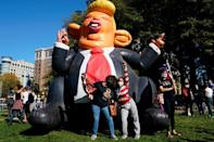 People celebrating the election of Democrat Joe Biden as US president pose by an inflatable caricature of Donald Trump as they celebrate near the White House on November 7, 2020