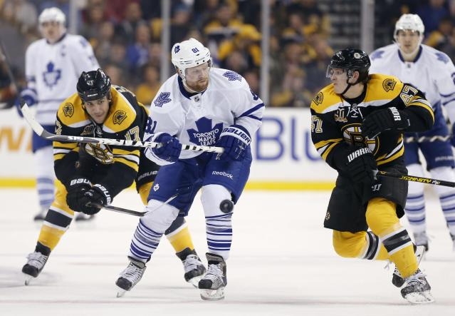 Boston Bruins' Torey Krug (47) and Milan Lucic (17) defend against Toronto Maple Leafs' Phil Kessel, center, in the first period of an NHL hockey game in Boston, Saturday, Nov. 9, 2013. (AP Photo/Michael Dwyer)