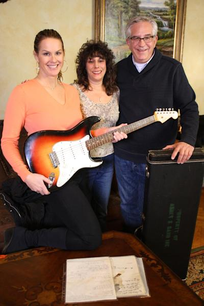 """This undated image released by PBS shows, from left, Elyse Luray, contributor Dawn Peterson and Wes Cowan, from """"History Detectives"""" with Bob Dylan's guitar. The electric guitar that Bob Dylan plugged in at the Newport Folk Festival in 1965 may be the most historic instrument in rock music, and it has sat mostly unnoticed in a New Jersey attic for most of the 47 years since. Dylan left it behind in an airplane and it was taken home by the pilot. The late pilot's daughter recently took it to PBS' """"History Detectives,"""" who authenticated the potentially fortune-making find in an episode that will air starting next Tuesday, July 17. (AP Photo/PBS, Tom McNamara)"""
