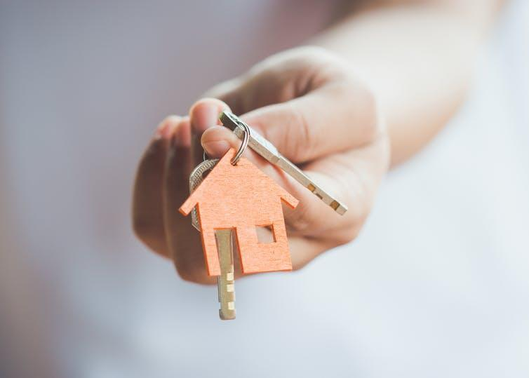 Hand holds out keys with a house-shaped keyring