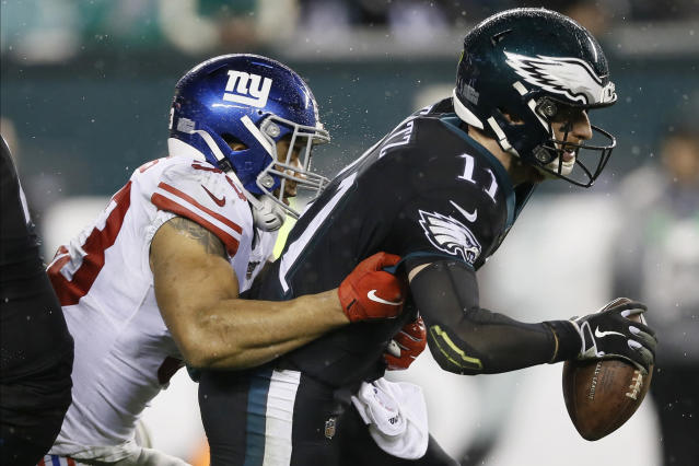 Philadelphia Eagles' Carson Wentz, right, is tackled by New York Giants' Oshane Ximines during the second half of an NFL football game, Monday, Dec. 9, 2019, in Philadelphia. (AP Photo/Michael Perez)