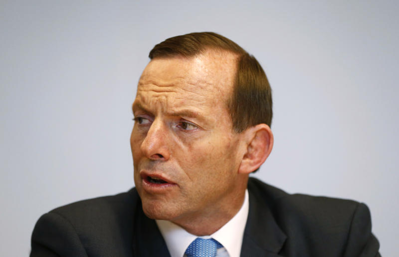 Australian Prime Minister-elect Tony Abbott meets with Treasury Secretary Martin Parkinson, in Sydney Sunday, Sept. 8, 2013. A new government prepared to take control of Australia on Sunday, with policies to cut pledges in foreign aid and to wind back greenhouse gas reduction measures in an effort to balance the nation's books. Abbott's conservative Liberal party-led coalition won a crushing victory at elections Saturday against the center-left Labor Party, which had ruled for six years. (AP Photo/Saeed KHAN, Pool)