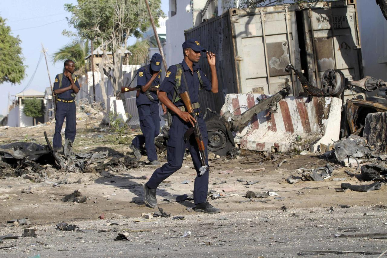 Security guards assess the aftermath at the scene of an explosion outside Jazira hotel in Mogadishu, January 2, 2014. Three bombs exploded within an hour outside the hotel in a heavily fortified district of the Somali capital on Wednesday, killing at least 11 people. REUTERS/Omar Faruk (SOMALIA - Tags: CIVIL UNREST DISASTER)
