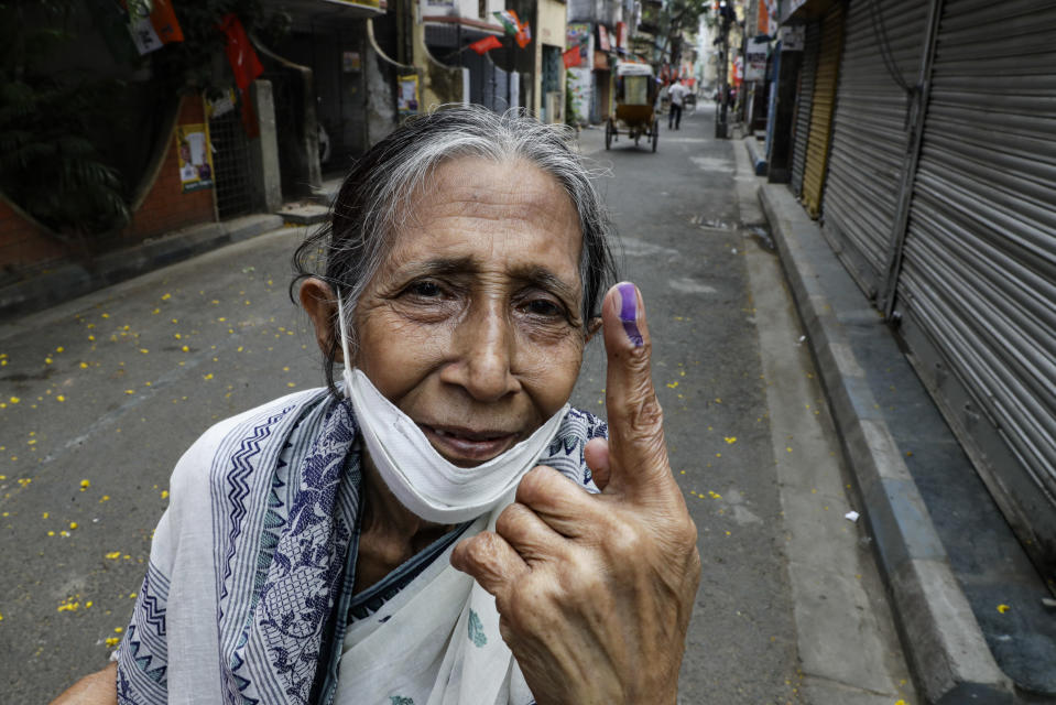 Bani Dasgupta, 75, displays the indelible ink mark after casting the vote during the fourth phase of West Bengal state elections in Kolkata, India, Saturday, April 10, 2021. (AP Photo/Bikas Das)