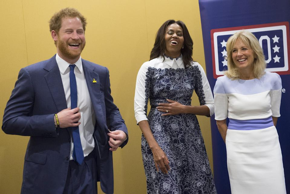 Harry, first lady Michelle Obama and Jill Biden laugh as they listen to a music presentation by wounded warriors at the USO Warrior and Family Center at Fort Belvoir, Virginia, on Oct. 28, 2015. (SAUL LOEB via Getty Images)