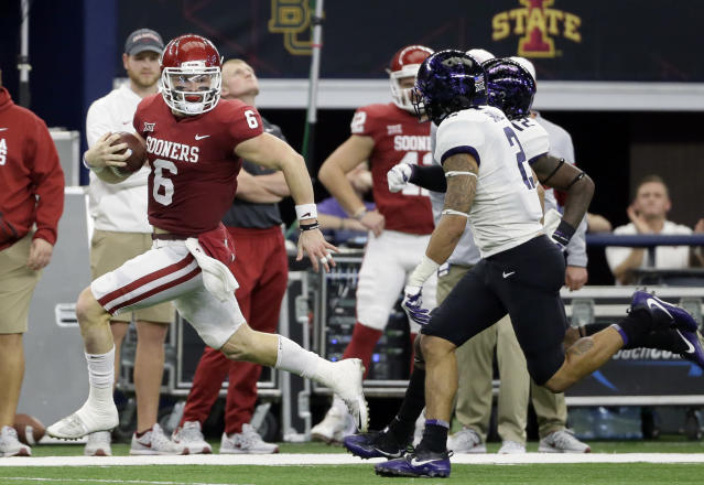Baker Mayfield (L) gains yardage as he runs the ball as TCU safety Niko Small (R) gives chase on Saturday, Dec. 2, 2017, in Arlington, Texas. (AP Photo/Tony Gutierrez)