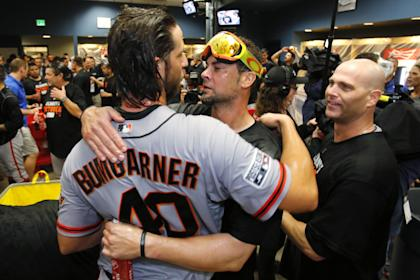 Giants pitcher Madison Bumgarner, left, hugs Ryan Vogelsong as they celebrate the team making the NLCS. (AP)