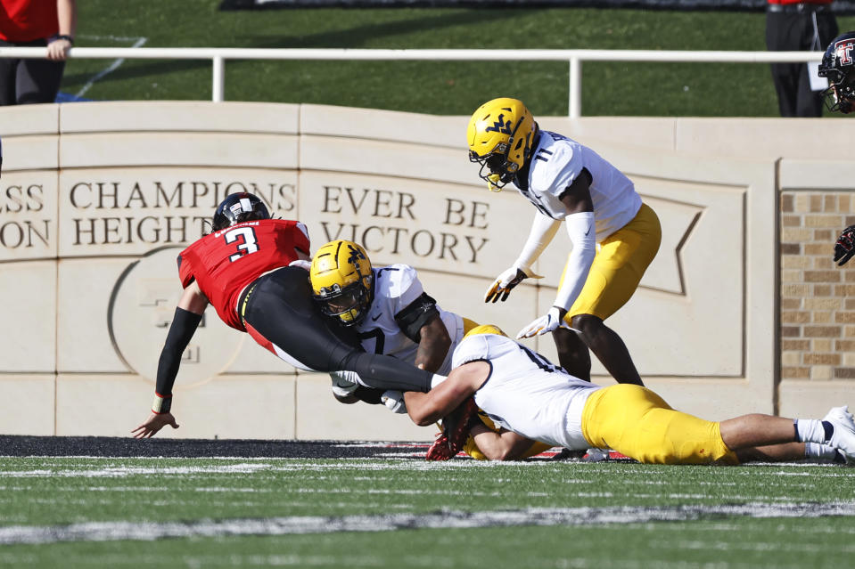 Texas Tech's Henry Colombi (3) lands in the end zone around West Virginia's Josh Chandler-Semedo (7) to score a touchdown during the first half of an NCAA football game against West Virginia, Saturday, Oct. 24, 2020, in Lubbock, Texas. (AP Photo/Brad Tollefson)