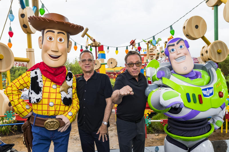 LAKE BUENA VISTA, FLORIDA - JUNE 08: In this Handout provided by Disney Resorts, Stars from DisneyPixars Toy Story 4 Woody (in costume), Tom Hanks (2nd-L), Tim Allen (2nd-R) and Buzz Lightyear (in costume) appear with characters from the film inside Toy Story Land at Disneys Hollywood Studios at Walt Disney World Resort on June 8, 2019 in Lake Buena Vista, Florida. (Photo by Matt Stroshane/Disney Resorts via Getty Images)