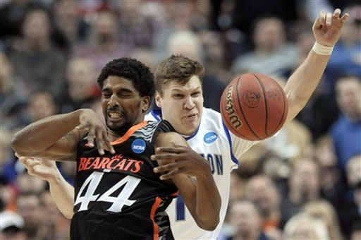 Cincinnati's JaQuon Parker, left, and Creighton's Grant Gibbs collide during the first half of a second-round game of the NCAA college basketball tournament, Friday, March 22, 2013, in Philadelphia. (AP Photo/Michael Perez)