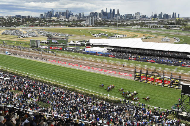 FILE - In this Nov. 1, 2016, file photo, horses cross the finish line in race five before the running of the Melbourne Cup horse race at the Flemington Racecourse in Melbourne. In Australia, where horse racing is arguably more popular than in any other country on the planet, the sport is continuing, minus the spectators, despite the nation's struggle to contain the new coronavirus. (AP Photo/Andy Brownbill, File)