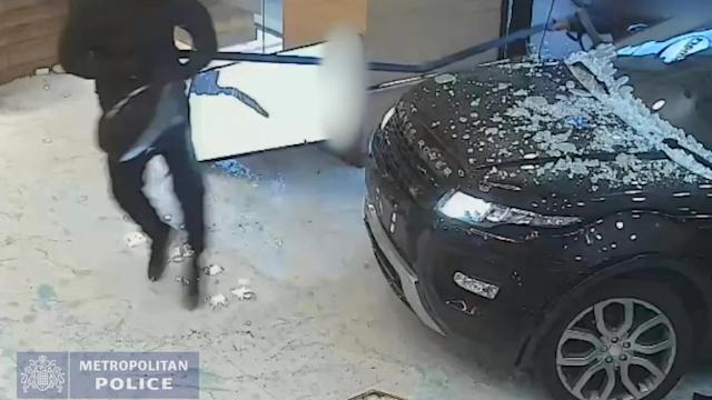 When the vehicle narrowly missed the people inside, the robbers got out and then smashed the glass display cases using a sledgehammer and a hammer, and put items of jewellery into bags (SWNS)