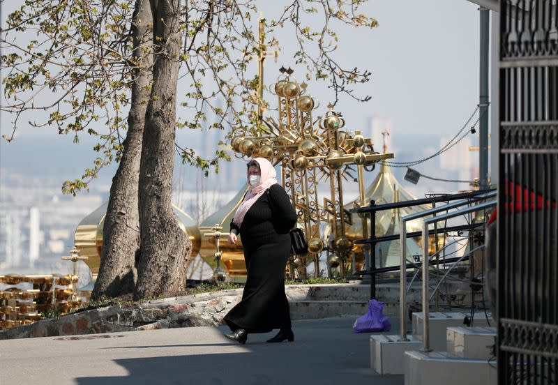 A woman wearing a protective face mask walks in the territory of the Kiev Pechersk Lavra monastery in Kiev