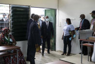 Ivory Coast President Alassane Ouattara, center, arrives to vote at a polling station during presidential elections in Abidjan, Ivory Coast, Saturday, Oct. 31, 2020. Tens of thousands of security forces deployed across Ivory Coast on Saturday as the leading opposition parties boycotted the election, calling President Ouattara's bid for a third term illegal. (AP Photo/Leo Correa)