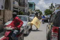 A man runs to get on a scooter and carry away a foam mattress after a group stole several of them from inside a Red Cross center in Les Cayes, Haiti, Friday, Aug. 20, 2021, six days after a 7.2 magnitude earthquake hit the area. (AP Photo/Matias Delacroix)