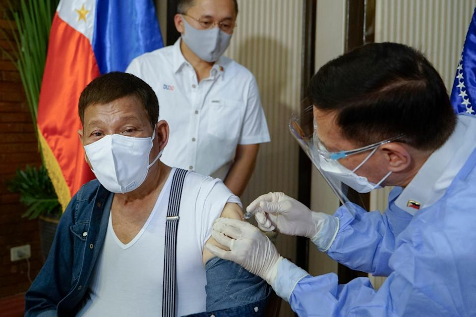 <p>In this photo provided by the Malacanang Presidential Photographers Division, Philippine President Rodrigo Duterte, left, is inoculated with China's Sinopharm Covid-19 vaccine by Health Secretary Fracisco Duque III at the Malacanang presidential palace in Manila, Philippines on3 May, 2021</p> (AP)