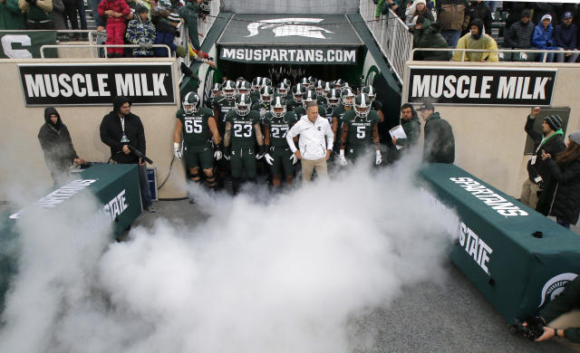 Michigan State coach Mark Dantonio, in white, and players prepare to take the field before an NCAA college football game against Penn State, Saturday, Nov. 4, 2017, in East Lansing, Mich. (AP Photo/Al Goldis)