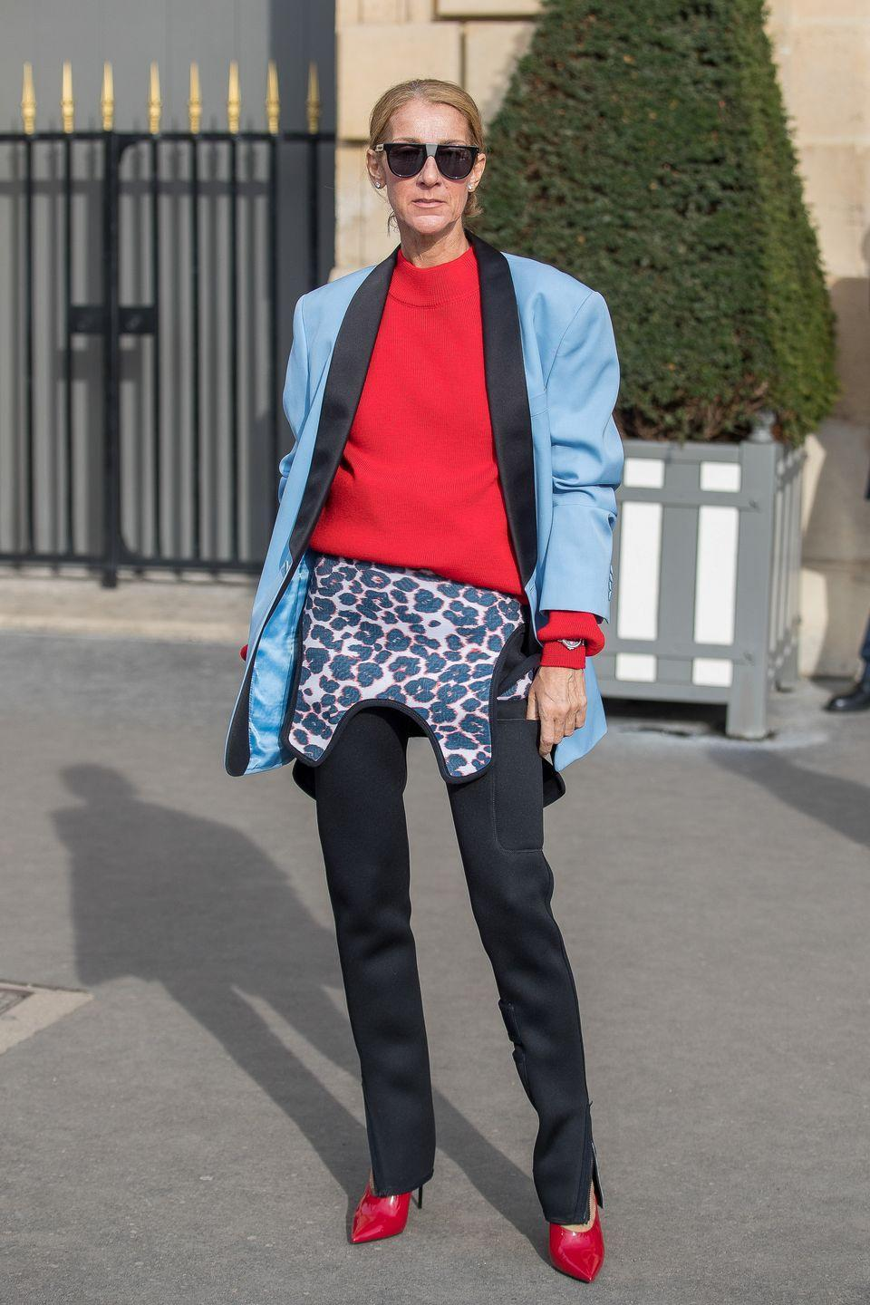 <p>Proving herself to be the Queen of layering, Dion paired a bright red sweater with a boxy blazer and reversible neoprene overalls. She finished off the look with classic red pumps and sunnies. </p>