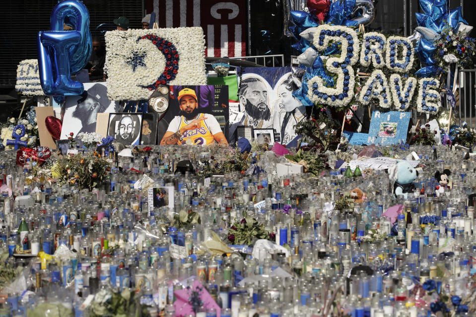 FILE - In thie April 11, 2019 file photo, a makeshift memorial site for slain rapper Nipsey Hussle is filled with candles outside The Marathon Clothing store in Los Angeles. Hussle, 33, was shot and killed outside his Los Angeles clothing store in Los Angeles on March 31, 2019. A year after Hussle's death, his popularity and influence are as strong as ever. He won two posthumous Grammys in January, he remains a favorite of his hip-hop peers and his death has reshaped his hometown of Los Angeles in some unexpected ways. (AP Photo/Jae C. Hong, File)