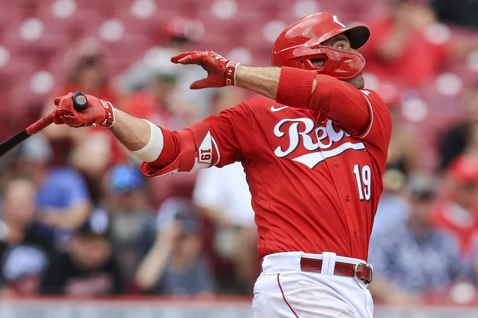 Cincinnati Reds' Joey Votto hits an RBI-single during the second inning of a baseball game against the Colorado Rockies in Cincinnati, Sunday, June 13, 2021. (AP Photo/Aaron Doster)