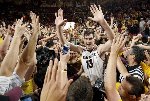 Arizona State's Jordan Bachynski (13) celebrates with fans after an NCAA college basketball game win against Arizona, Friday, Feb. 14, 2014, in Tempe, Ariz. Arizona State defeated Arizona 69-66 in double overtime. (AP Photo/Ross D. Franklin)