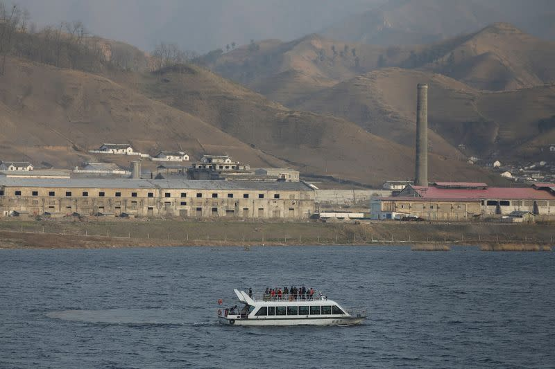 Chinese cruise boat passes buildings in North Korea's Sinuiju on the Yalu River, in Dandong