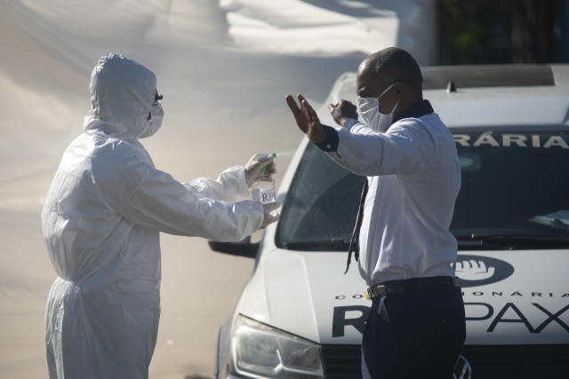 Funeral service employees, cleaning up with alcohol, at the field hospital for corona virus patients, covid 19, Barra da Tiuca, west of the city, on May 12, 2020. (Photo by Fabio Teixeira/NurPhoto via Getty Images)