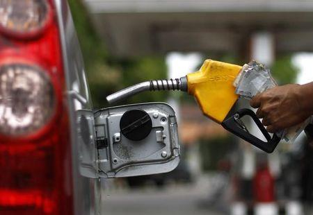 A worker fills a tank with subsidized fuel at a fuel station in Jakarta