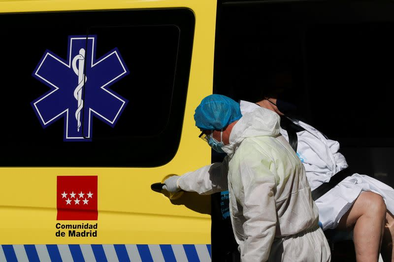 FILE PHOTO: A healthcare worker in protective gear assists a patient into an ambulance outside the emergency unit of the Hospital Universitario La Paz during the coronavirus disease (COVID-19) outbreak in Madrid