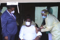 Zimbabwean President Emmerson Mnangagwa, centre, receives his shot of the Chinese Sinovac COVID-19 vaccine in Victoria Falls, Wednesday March 24, 2021. Mnangagwa got his jab in the resort town of Victoria Falls, in a bid to promote tourism and launch the second phase of the countrys vaccination drive.(AP Photo/STR)