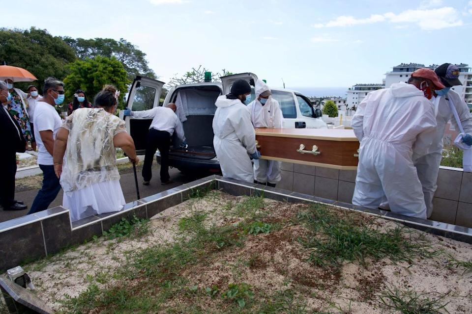 Gravediggers, wearing protections, carry the coffin a person who died from the Covid-19 at Uranie Cemetery in Papeete in French Polynesia.