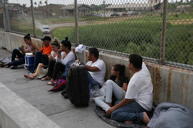 """<span class=""""s1"""">Asylum seekers wait on the Mexican side of the Brownsville-Matamoros International Bridge on July 25 after being denied entry by ICE officers. (Photo: Loren Elliott/Reuters)</span>"""
