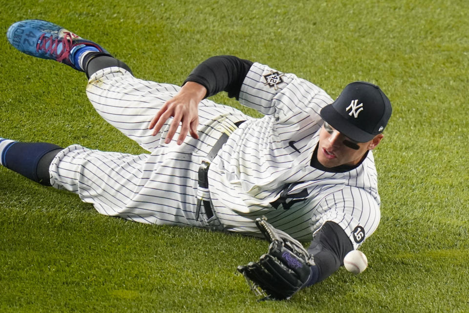 New York Yankees' Aaron Judge dives for a ball hit by Tampa Bay Rays' Manuel Margot during the sixth inning of a baseball game Friday, April 16, 2021, in New York. Margot singled. (AP Photo/Frank Franklin II)