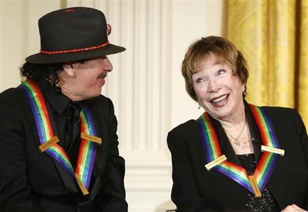 Santana and fellow 2013 Kennedy Center Honors recipient MacLaine react to remarks by U.S. President Obama during a reception at the White House in Washington