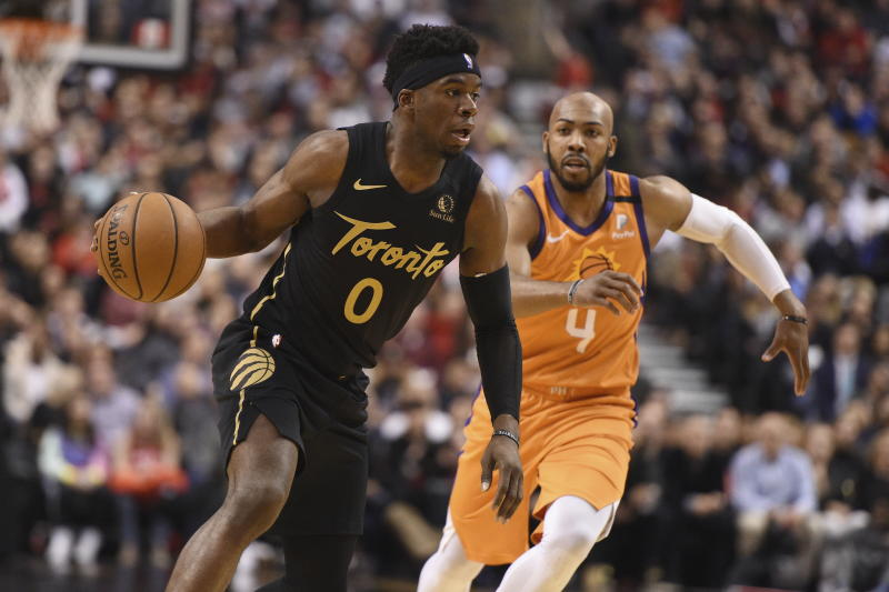 Toronto Raptors guard Terence Davis (0) is defended by Phoenix Suns guard Jevon Carter (4) during the second half of an NBA basketball game Friday, Feb. 21, 2020, in Toronto. (Frank Gunn/The Canadian Press via AP)