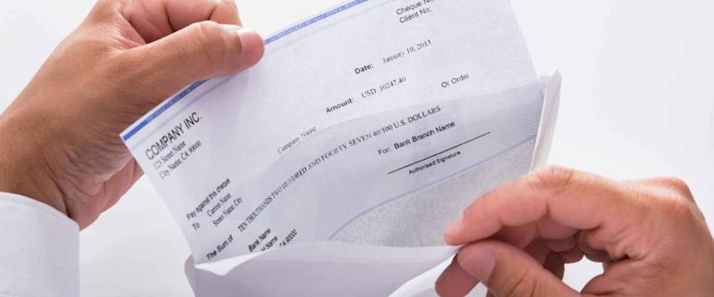 Close-up of a businessman's hand opening envelope with paycheck