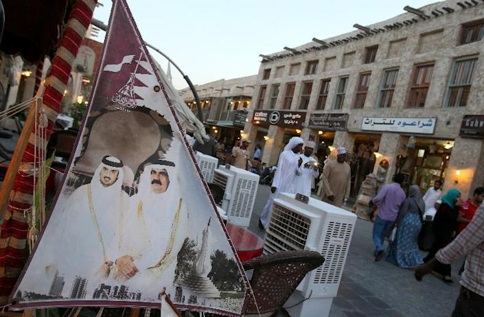 People walk past a banner bearing portraits of former emir of Qatar Sheikh Hamad bin Khalifa al-Thani (R) and his son Sheikh Tamim (L), who acceded to the throne one year ago, in Doha on June 25, 2014 (AFP Photo/Karim Jaafar)