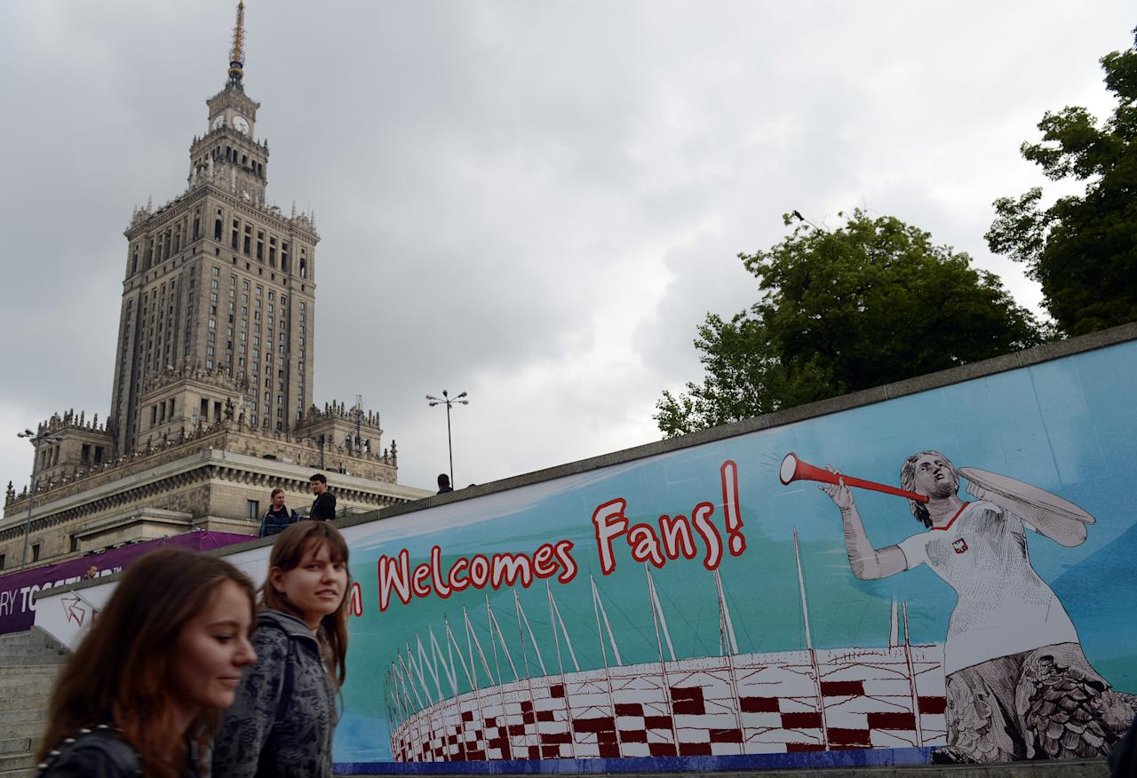 Two women walk by the Euro 2012 football fanzone near the Palace of Culture in the center of Poland's capital Warsaw.