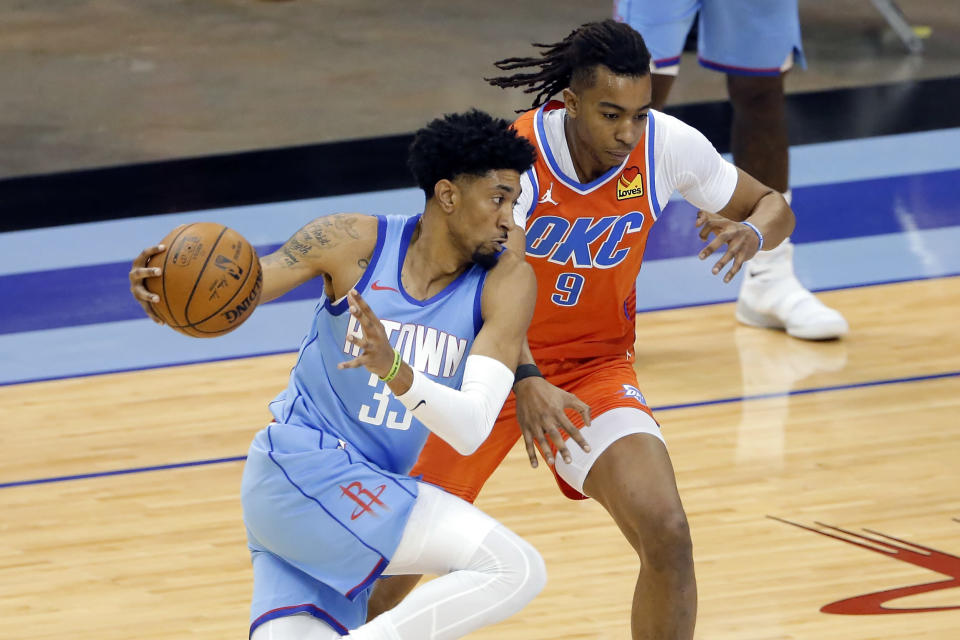 Houston Rockets center Christian Wood (35) drives past Oklahoma City Thunder center Moses Brown (9) during the first half of an NBA basketball game Sunday, March 21, 2021, in Houston. (AP Photo/Michael Wyke)