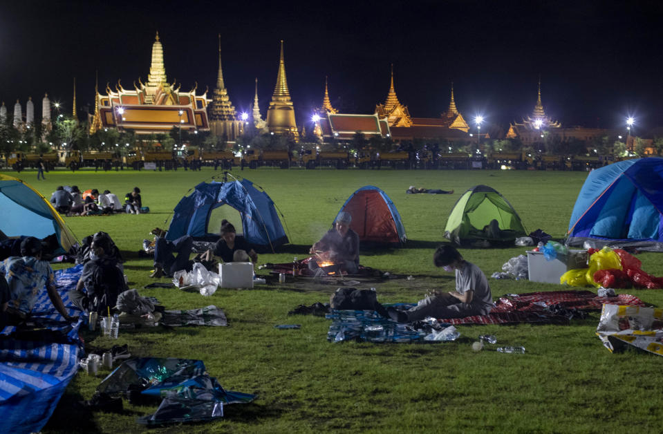 Pro-democracy protesters who occupied Sanam Luang, a historic field for an over-night protest rally, cook a meal in Bangkok, Thailand, early Sunday, Sept. 20, 2020. Thousands of demonstrators turned out Saturday for a rally to support the student-led protest movement's demands for new elections and reform of the monarchy. (AP Photo/Gemunu Amarasinghe)