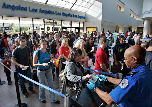 Travelers form a long security check line that is extended out of departure lounge at Los Angeles airport.
